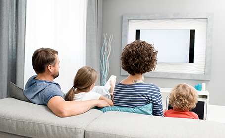 Back view portrait of family with two kids watching TV sitting on sofa in living room at home